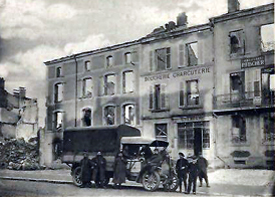 french lorry with personnel by bombed damaged buildings